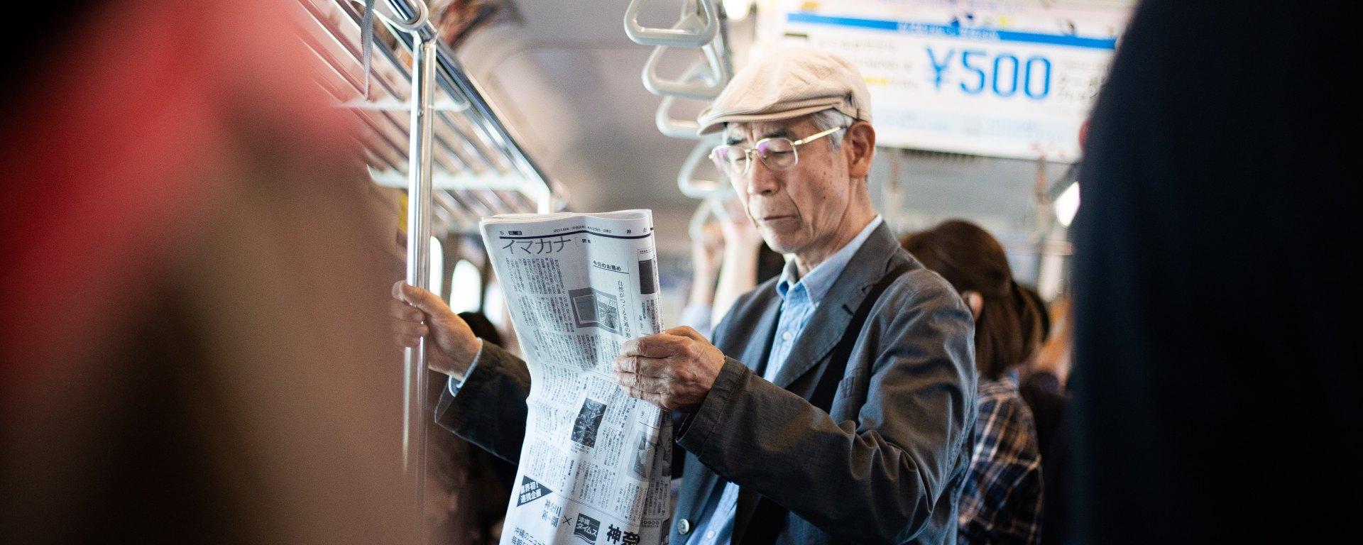 man reading a Japanese newspaper