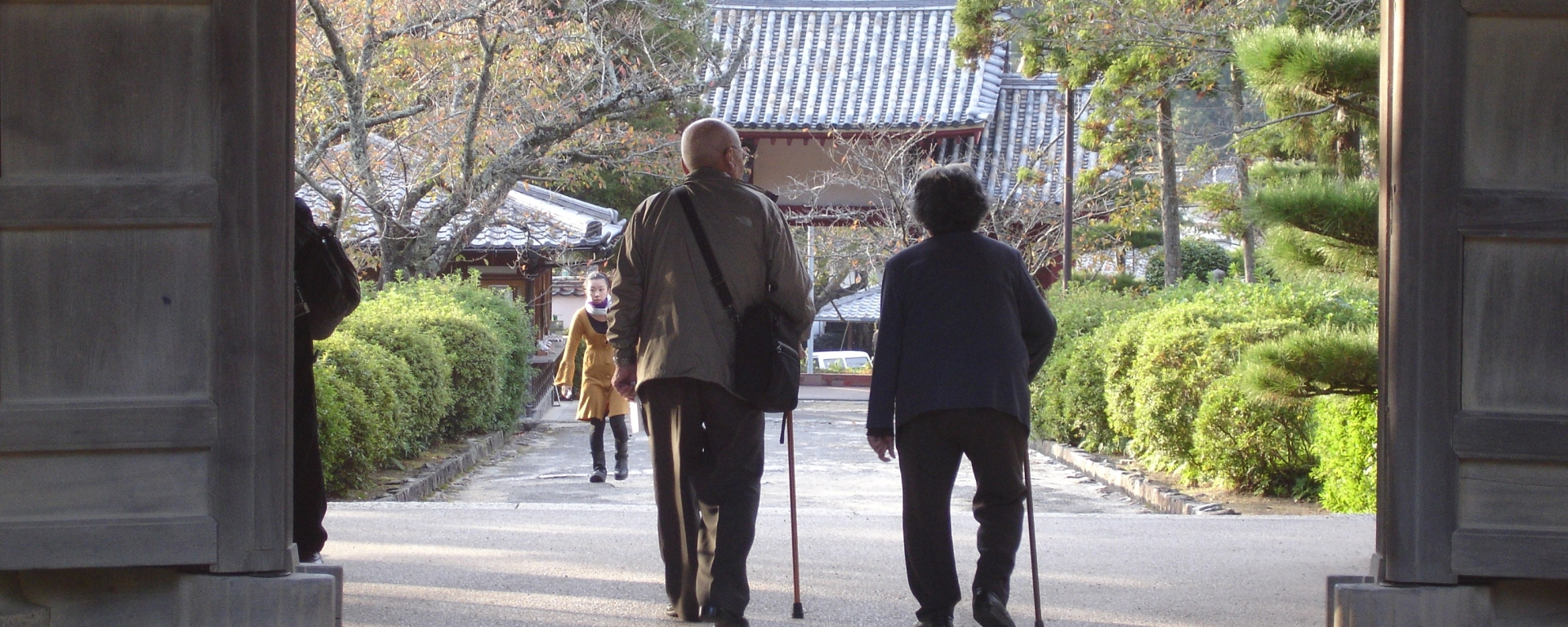 An elderly couple uses canes to walk through a gate at a temple in Hagi