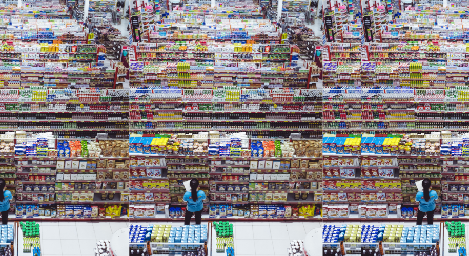 A woman reads labels in a large grocery store